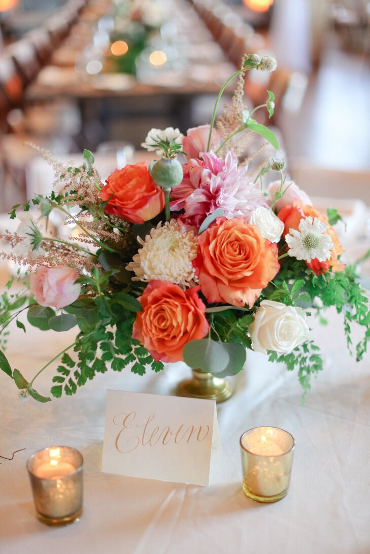 Low, lush arrangements of coral garden roses, football mums, dahlias, astilbe, scabiosa, maidenhair fern, jasmine vine, and silver dollar eucalyptus in gold pedestal vases topped the round reception tables.