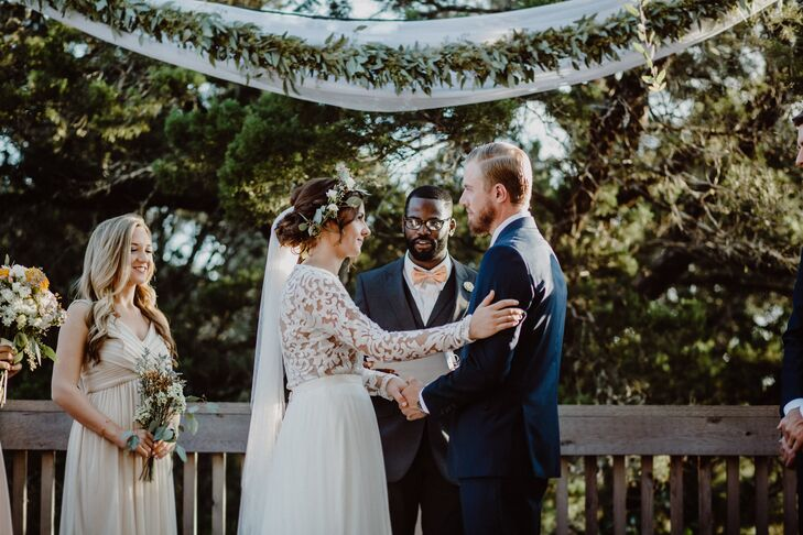 Plenty of greenery plus simple white draping and a slender green garland served as the backdrop for Emily and Jonathan's vows at the Greenhouse at Driftwood in Driftwood, Texas.