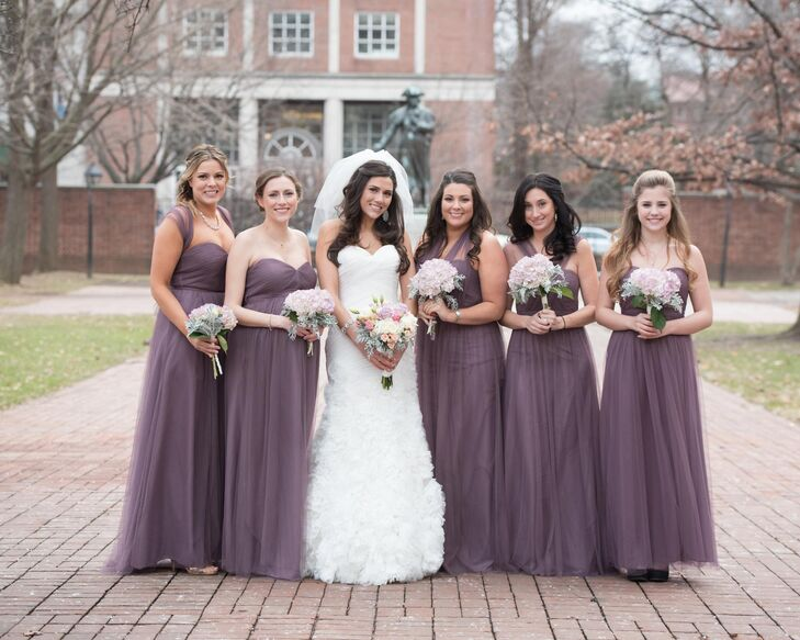 Karen's bridesmaids wore floor-length chiffon dresses by Jenny Yoo. The pretty dresses were in a soft, muted shade of plum that was perfect for the winter wedding. As a bonus their convertible necklines meant the bridesmaids could wear them in the style of their choosing. The bridesmaids carried bouquets of pink hydrangeas and dusty miller with their soft purple dresses.
