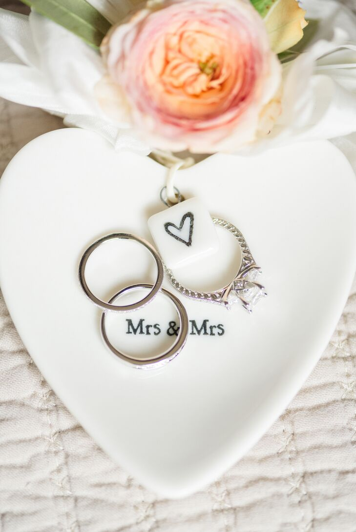 "Andrea and Mariko's wedding rings in a heart-shaped ""Mrs. & Mrs."" ring dish—rings were designed by Steve Padis Jewelry."