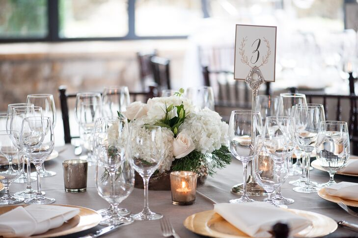 The round tables at the reception were topped with white hydrangeas, blush roses and white lisianthus in low bronze metallic vases. Gold mercury glass votives added plenty of romance, and Emily and Edward used the same design motif from the invitations for the table numbers.