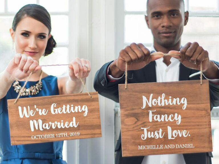 Couple holding custom wooden engagement signs