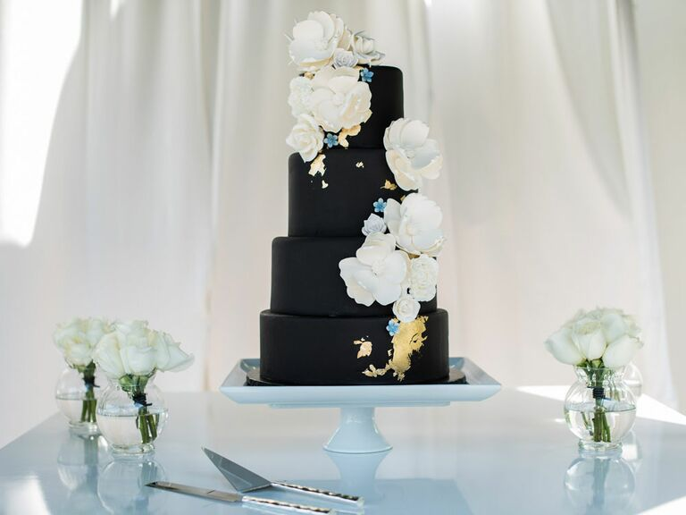 Four-tier black wedding cake with gold foil and white flowers