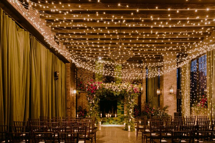 Romantic, Industrial Ceremony Site with String Lights and Flower Arch