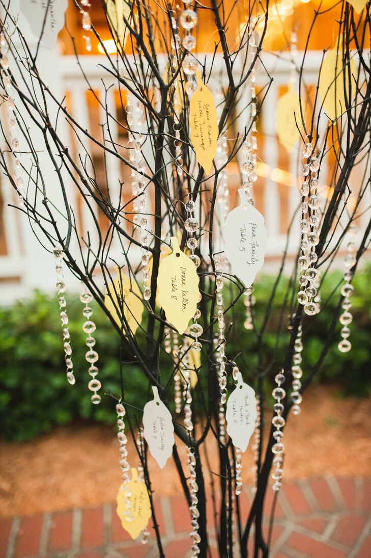 The tree motif also carried into their cocktail hour. After guests enjoyed passed bacon-wrapped meatballs, spanakopita and bruschetta, they all stopped by the couple's whimsical place card display. Every yellow or gray leaf-shaped card hung from crystal-draped branches with the guests' names and table numbers.