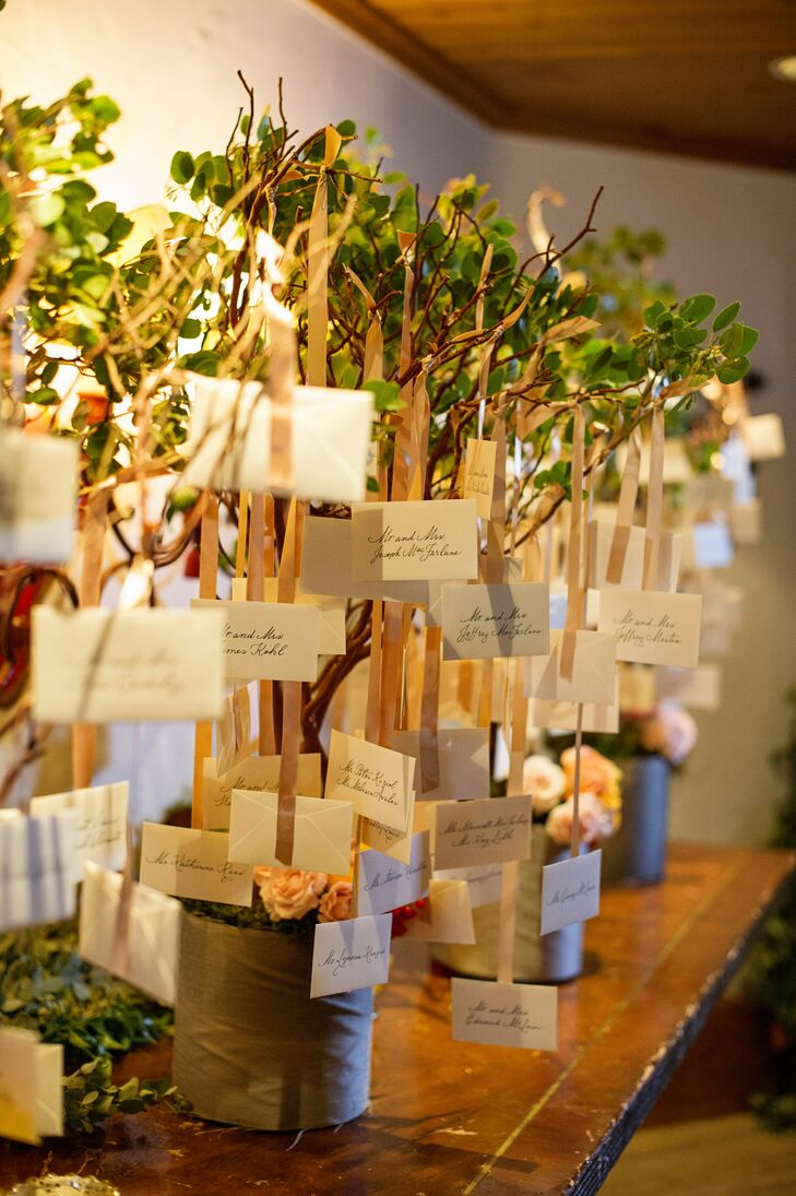 The escort cards were displayed hanging from potted trees with champagne satin ribbons for a whimsical indoor garden feel.