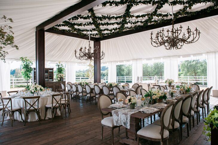 Under the elegant white tented reception space in Santa Barbara, California, dark wood beams connected to the ceiling that had elegant chandeliers dangling from above. Some dining tables had lace runners draped down the middle of bare wooden tops, while others had white tablecloths covering the entire surface.