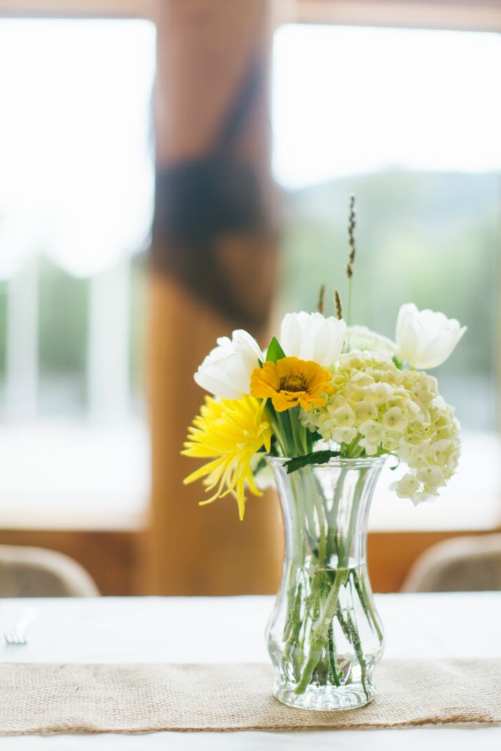 A small arrangement of yellow and white wildflowers added a charming, rustic touch to the centerpiece decor.