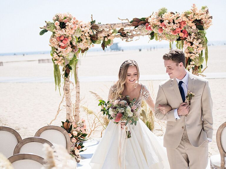 Bride and grom at a beach wedding with a flower arch