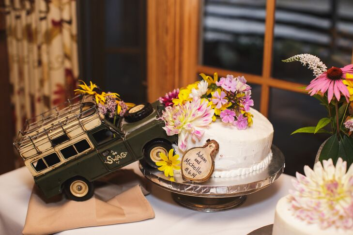 """Unbeknownst to the bride, the bakery forgot to make the couple's cake until day of the wedding and then the entire cake slid during the drive to the venue. """"Needless to say, the cake did not survive the attack and Adam had suggested that they take a model land rover and place it into the side of the cake,"""" says Michelle. """"We all laughed when we saw it!"""""""