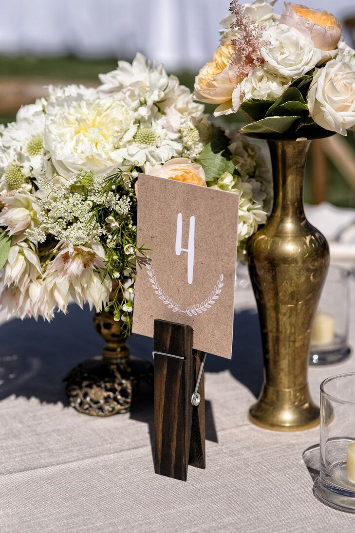 Dining tables were marked with numbers written in white and displayed on pieces of sandpaper. The table numbers were surrounded by elegant, neutral-color flower centerpieces filled with a variety of roses, hydrangeas and peonies.