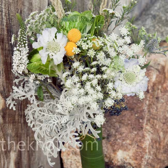 """""""Simple and organic"""" was how the bride described thistle, Dusty Miller, white wax flowers, wheat grass and scabiosa in her bouquet."""