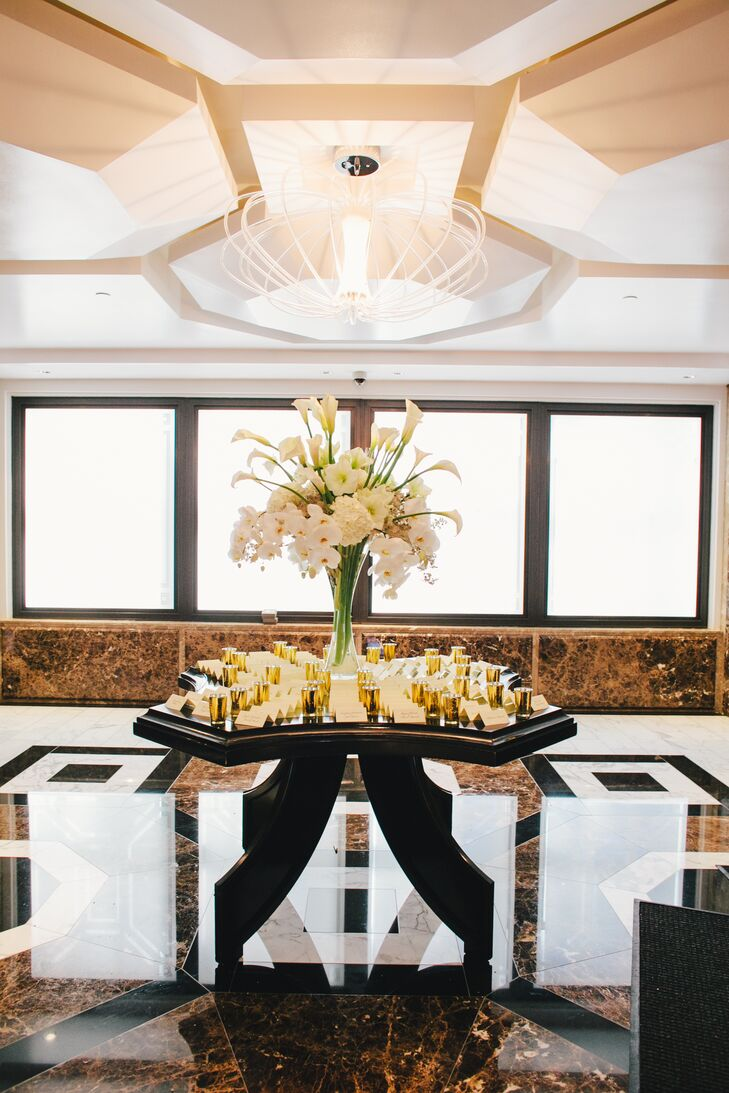 Ivory escort cards were organized next to gold shot glasses on an elegant mahogany wood table. A lush arrangement of ivory orchids, peonies, calla lilies and hydrangeas was positioned behind the cards.