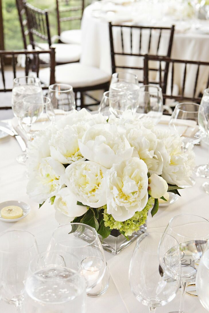 The couple chose low centerpieces for the reception, each table incorporating flowers found in the bridal and bridesmaid bouquets. It was important to Brian and I that we avoid tall arrangements that might impede conversation, says Fanny.