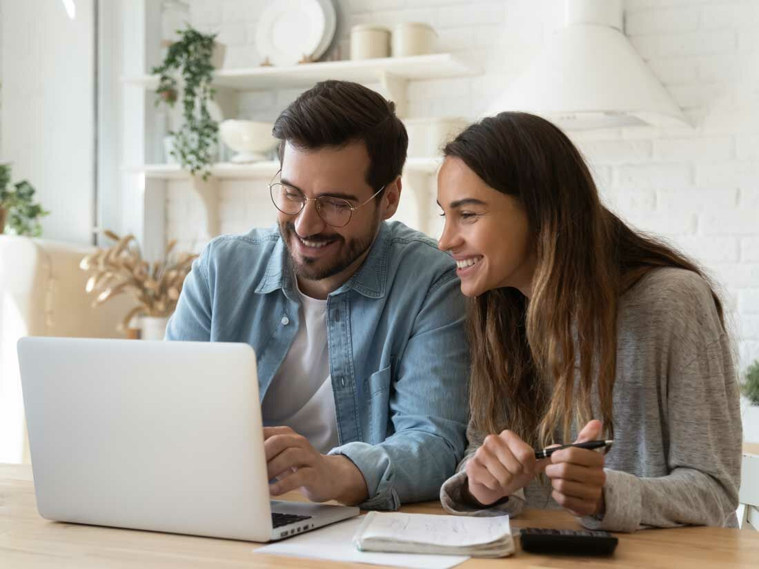 Couple at home using laptop