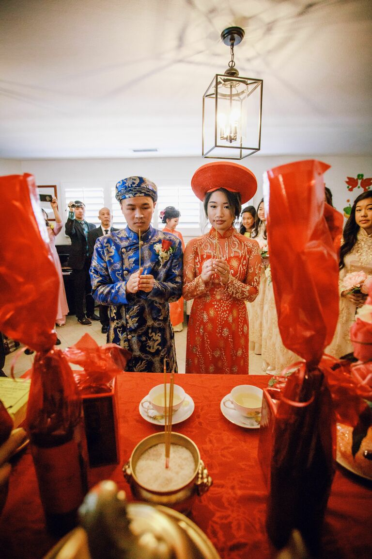 Couple praying at altar during Vietnamese wedding ceremony