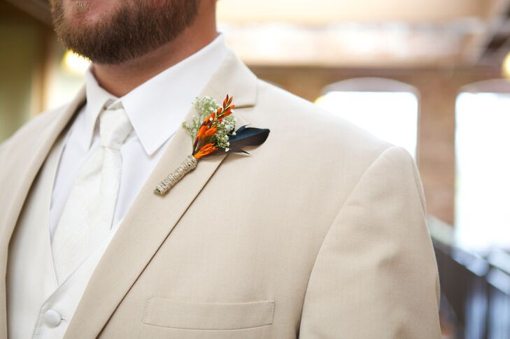 Brandon's love of duck hunting definitely came out in his boutonniere. He wore an arrangement with a blue duck feather, dried orange freesias and baby's breath wrapped in twine.