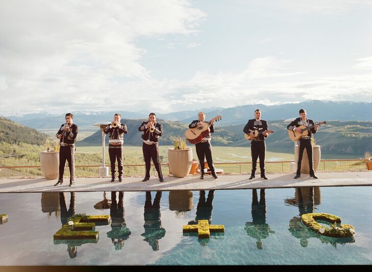 "After the ceremony, guests were invited down the two cascading staircases to the pool. Situated facing the dramatic Wyoming mountains, the pool was the perfect location to place floating letters spelling ""Katie + Cody."""