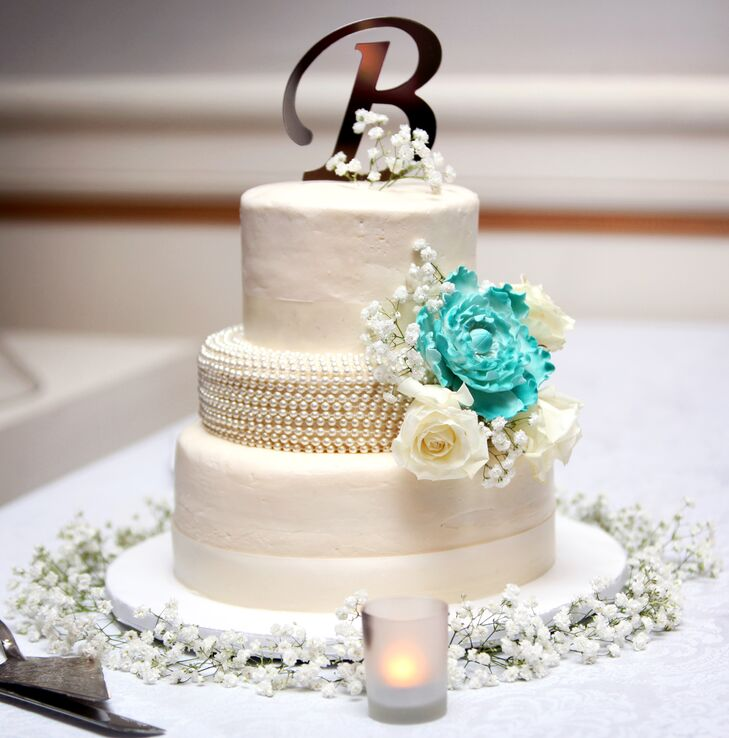 Molly and Andrew's white wedding cake had a middle tier covered in pearls. The middle tier was also decorated with ivory roses, baby's breath and a teal cake flower. The cake was topped with a silver monogram and surrounded by baby's breath.