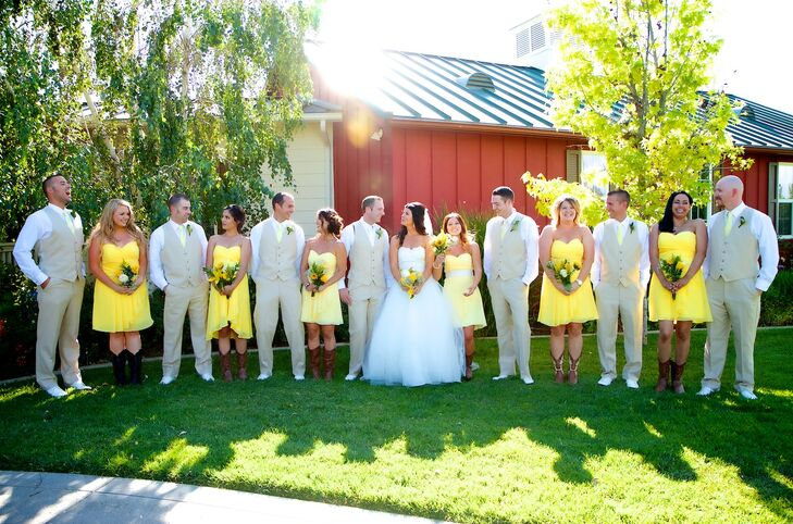 The couple stood in the middle of their wedding party in front of the red barn reception venue. The bridesmaids wore bright yellow dresses while the men wore tan vests and pants.