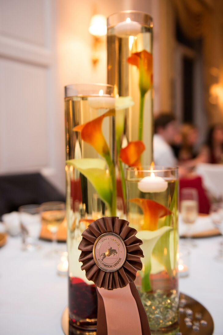 Centerpieces at the reception consisted of cylinder glass vases of varying heights filled with calla lilies and floating candles.