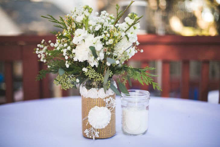 Roxanne decorated mason jars with burlap and lace and filled them with white wildflowers for rustic, winter country-inspired table centerpieces.