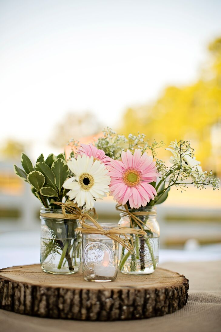 Mixed arrangements of roses, gerber daisies and baby's breath filled rustic mason jars.