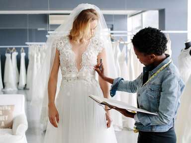woman trying on wedding dresses at bridal salon with consultant