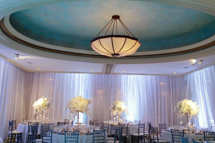 Light blue uplighting, gauzy white draping and lush white floral arrangements provided the simple, soothing color palette for the reception.