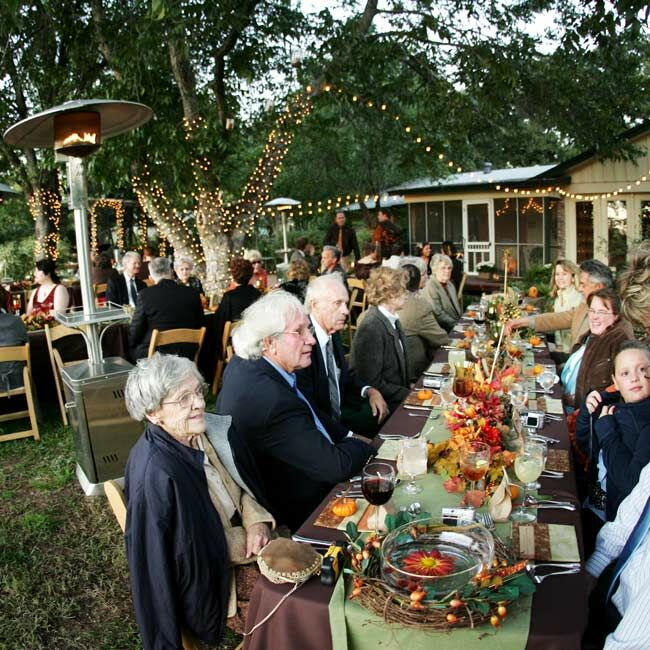 Tatiana and Chris' tables reflected a bounty of autumn-inspired decor. The bride, her mother, and her sister spent months preparing the details, from fall shapes carved into papier-mache pumpkins to incorporating the guinea hen feathers the father of the bride collected. Green- and amber-hued candleholders added to the fall ambience.