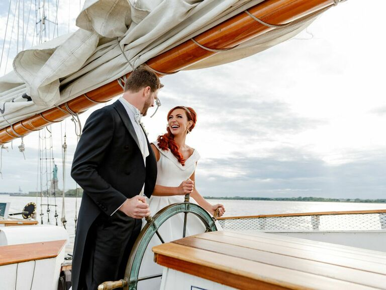 Bride and groom steering boat at nautical-themed wedding