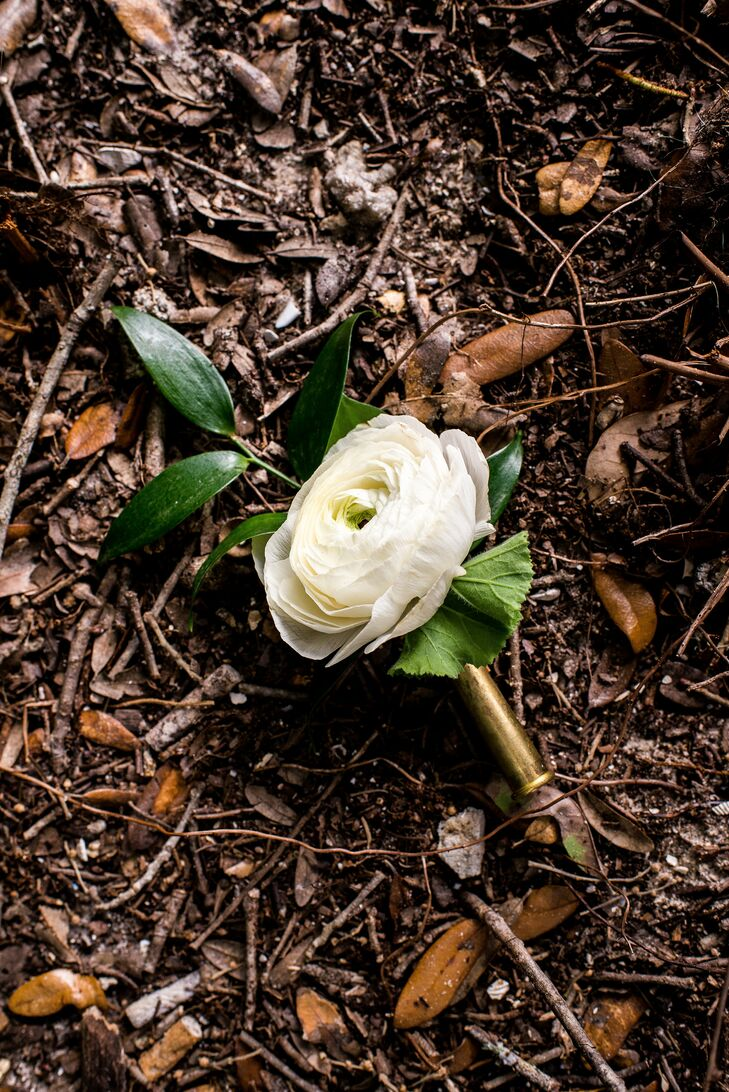 Landon, his and Angela's fathers and the groomsmen had boutonnieres with a personal touch. Single white peonies and ranunculus were placed in actual shell casings Angela had collected.