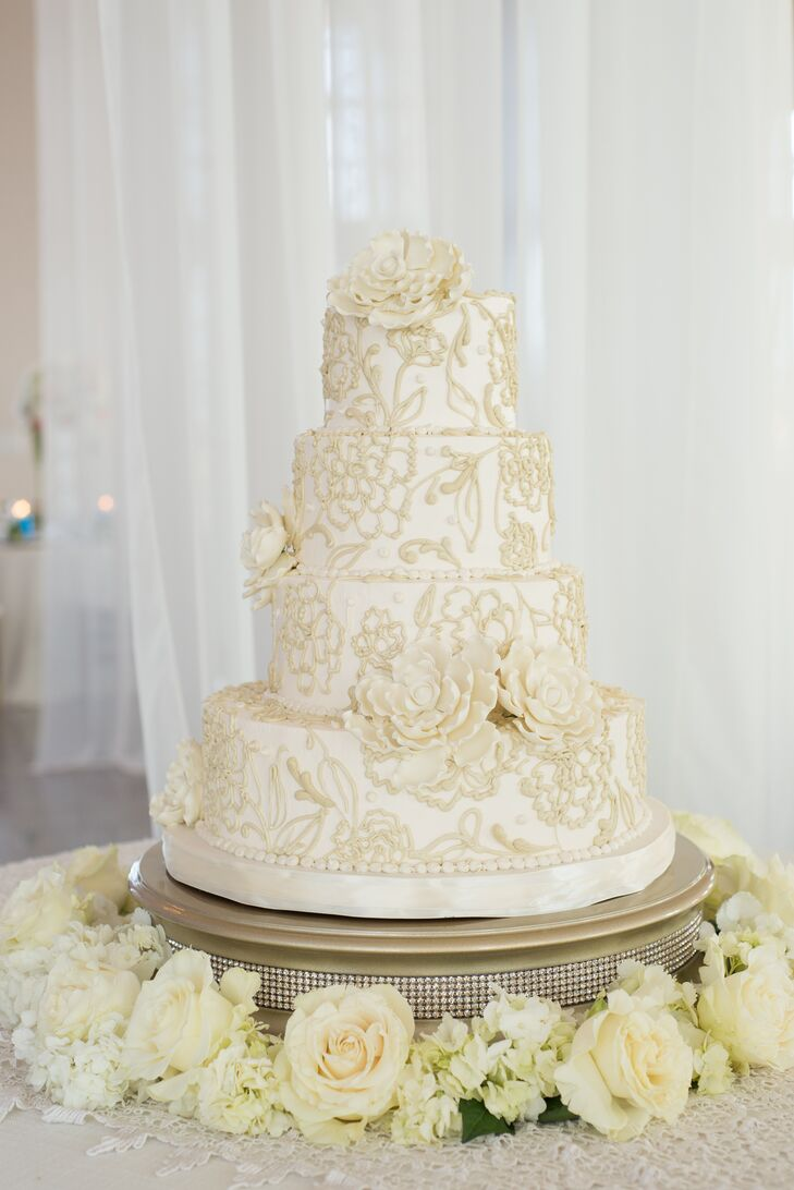 Honey's Cakes created a stunning four-tier cake with exquisite ivory floral details and sugar flowers. A wreath of ivory flowers surrounding the gold cake stand, embellished with rhinestones, completed the eye-catching display.