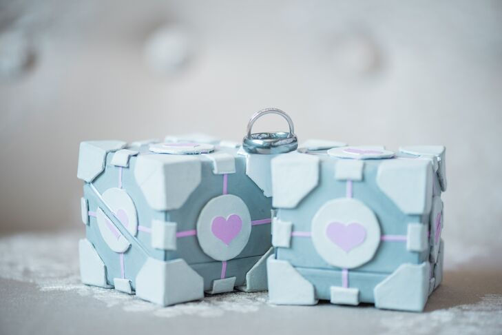 The companion cube from the video game Portal 2, a first-person-perspective puzzle, doubled as the ring boxes. Jess and Dave made the boxes with chipboard, various types of paper, watercolor paints and glue.