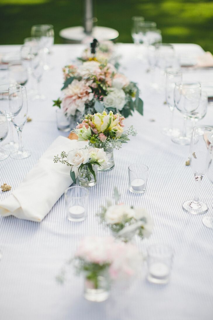 Setting a relaxed tone for dinner that encouraged guests to interact was essential for Molly and Patrick. The florists at Daisy Rose took that to heart when creating the reception centerpieces. They arranged a series of small bundles of roses, dahlias, peonies and eucalyptus in bud vases, which allowed guests to talk with ease.