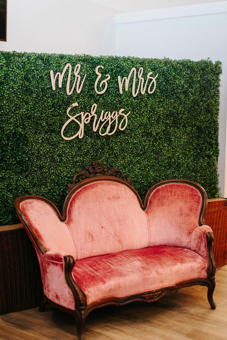 Boxwood wall with velvet sofa for photo booth
