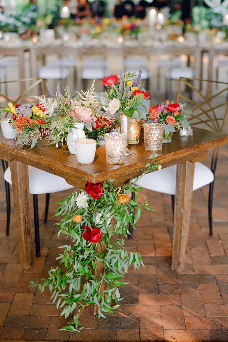 Maggie and Joe sat at a reclaimed-wood sweetheart table, draped in a garland of seasonal blooms.