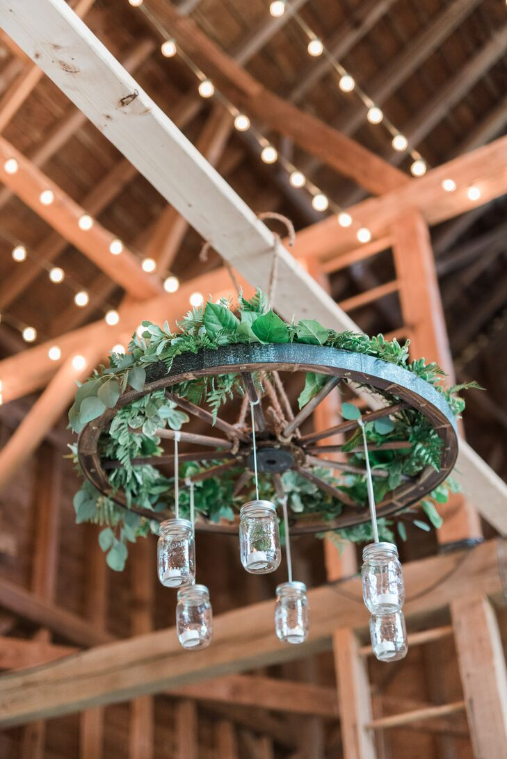 Rustic Wheel Chandelier with Hanging Mason Jars and Greenery