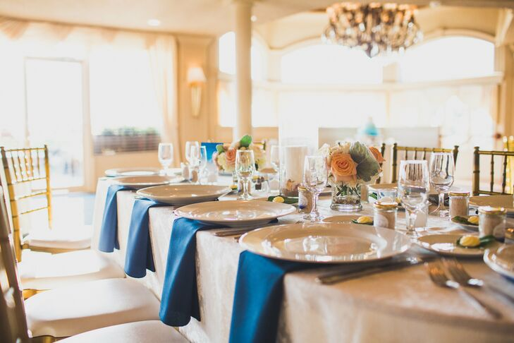 As with the rest of their decor, Jodi and Joe chose an understated, nautical design for the reception tables. Paired with gold chiavari chairs and ivory linens, each place setting included a bold navy napkin draped along the edge and matching ivory dinnerware. A mini arrangement of roses, dusty miller and hydrangeas, which matched the bridesmaid bouquets, stood out in between each one. Candles in seashell-filled vases also accented the tablescape.