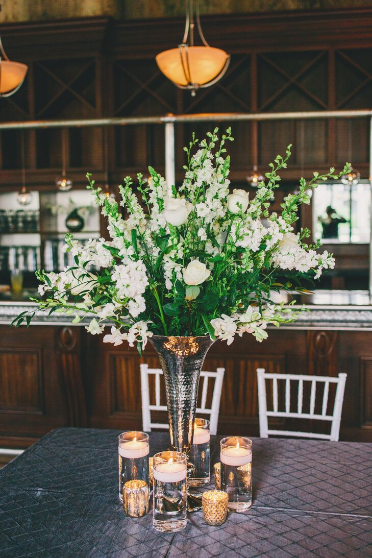 The reception tables were topped with antique silver vases filled with lush white floral arrangements including roses, sweet peas and orchids. Kinsey and Collins loved how the centerpieces brought the outside in and gave a simple, timeless feel to the soiree.