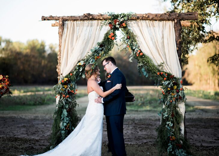 "The ceremony arch was built with cedar from Jogee's family's farm in Mississippi. Jogee's father and the groomsmen assembled the arch, and the florist hung the curtains and placed the flowers. The green trimmings on the arch and tables were also collected from the family farm. ""I will never smell a cedar tree again and not think of my wedding day, my wonderful husband and my family,"" Jogee says."