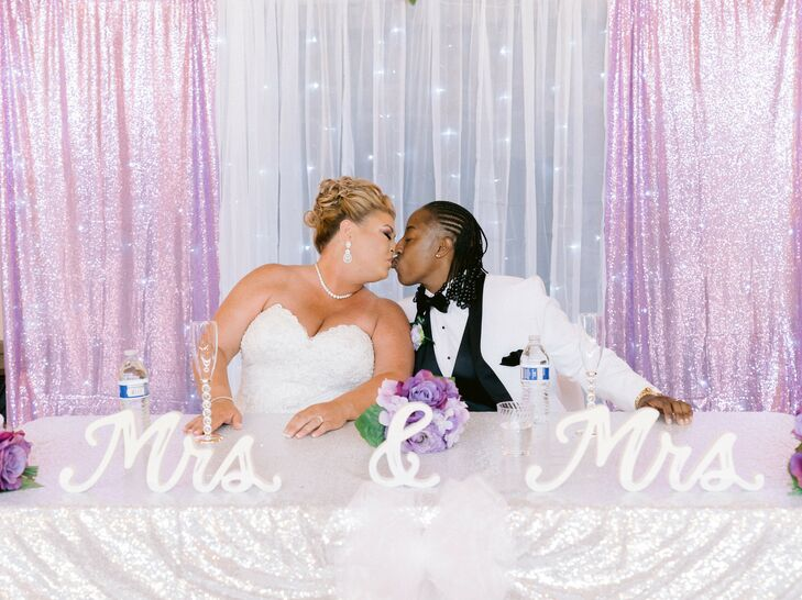 Couple Sharing Kiss at Sweetheart Table During Reception