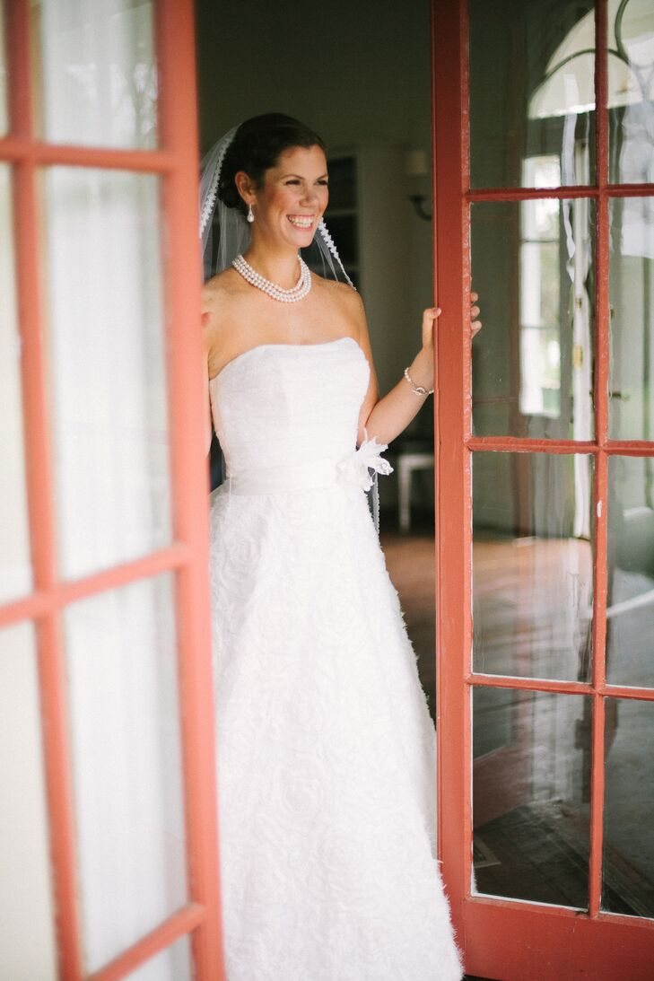 Laine wore a strapless, A-line wedding dress with rosettes on the skirt from Kleinfeld. She accessorized with a flowery belt and pearl jewelry.