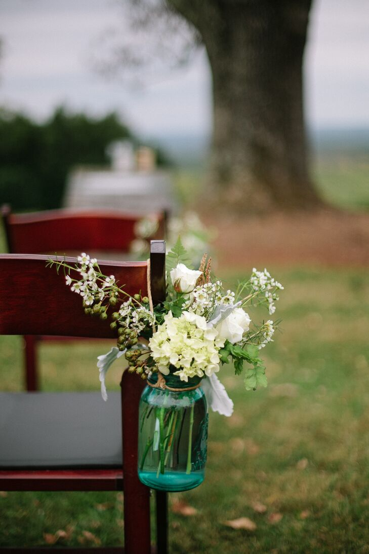 Small jars with arrangements of white hydrangeas, white rose, hypercium and dusty miller adorned the aisle at the outdoor ceremony.