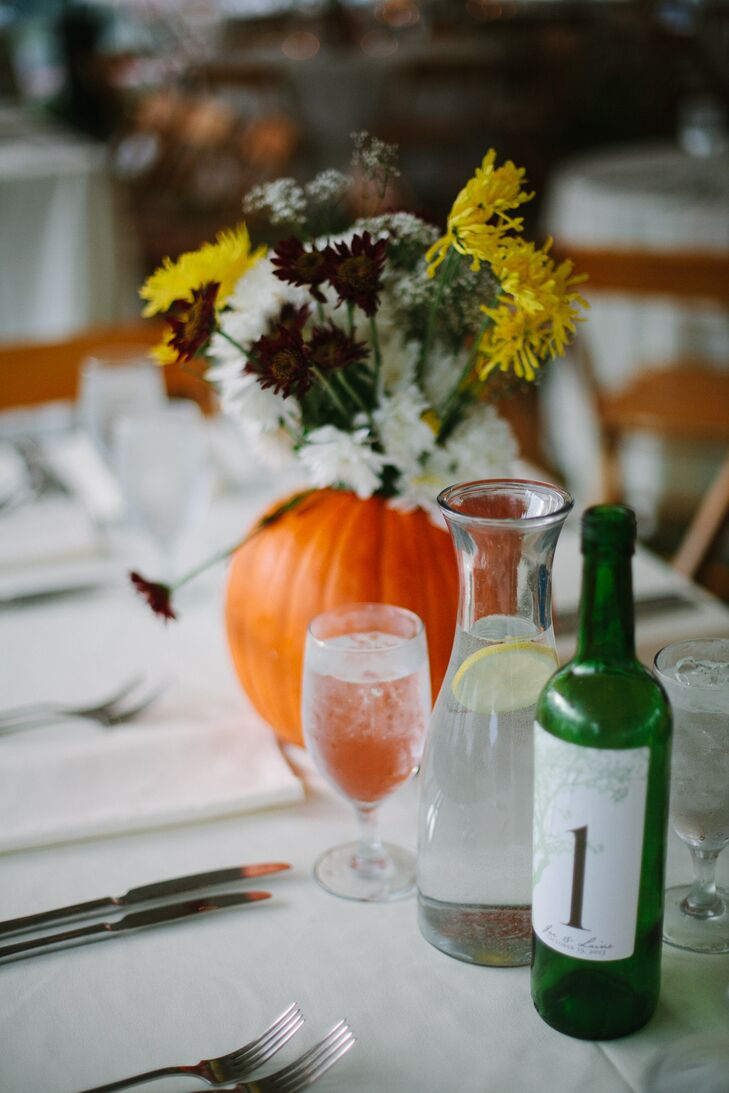 Centerpieces at the fall reception featured vases made out of pumpkins and filled with yellow, dark purple and white daisies. Table numbers were indicated by wine bottles, which was appropriate for the vineyard setting.