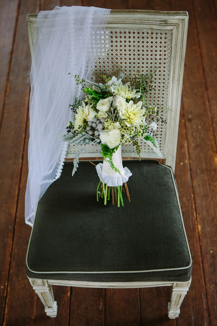 Laine's bouquet consisted of white dahlias, white ranunculus, silver brunia, green hypercium and dusty miller.