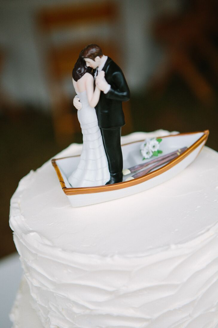 The cake topper featured a bride and groom slow dancing on a row boat as a nod to the couple's love of sailing. The wedding cake, flavored chocolate with raspberry ganache, was made by a close friend.