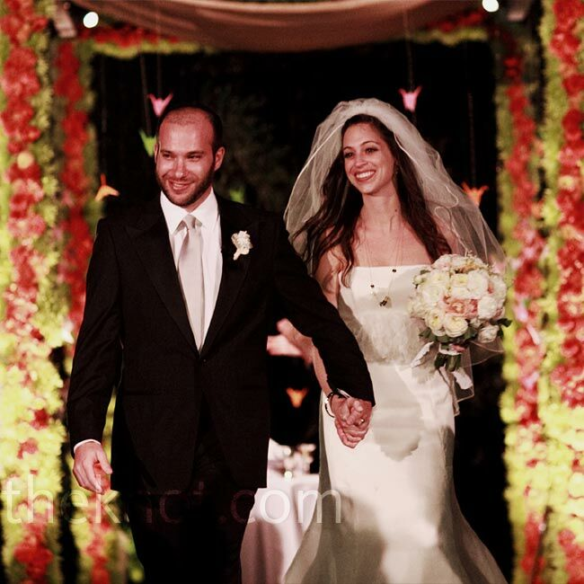 The couple exchanged vows beneath a floral huppah decorated with strands of hanging paper cranes.