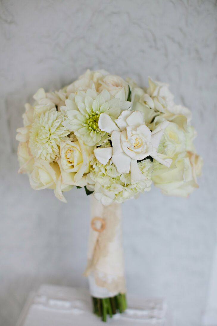 Sarah's bouquet was wrapped with a sleeve from her grandmother's wedding dress and pinned with a gold circle that was passed down to her from her mother, symbolizing marriage as unbreakable.