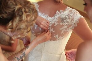 Bride Getting Buttoned Up in Dress